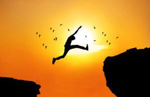 Man leaping between boulders in sillouhette