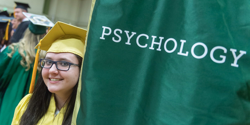 Female graduate in yellow gown with Psychology banner