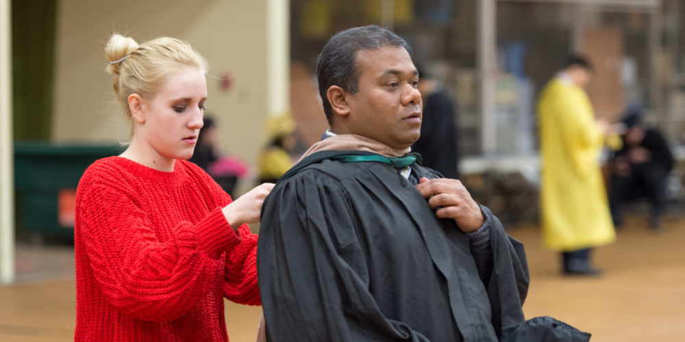 Woman helps graduate with his regalia