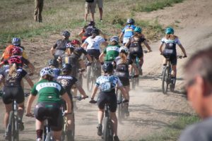 Cyclists take off all together on a dirt road.