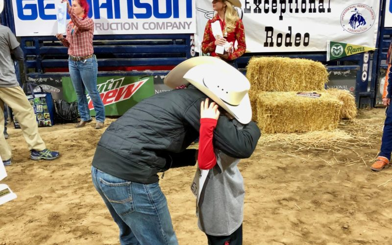 Cowboy hugs participant at Exceptional Rodeo.