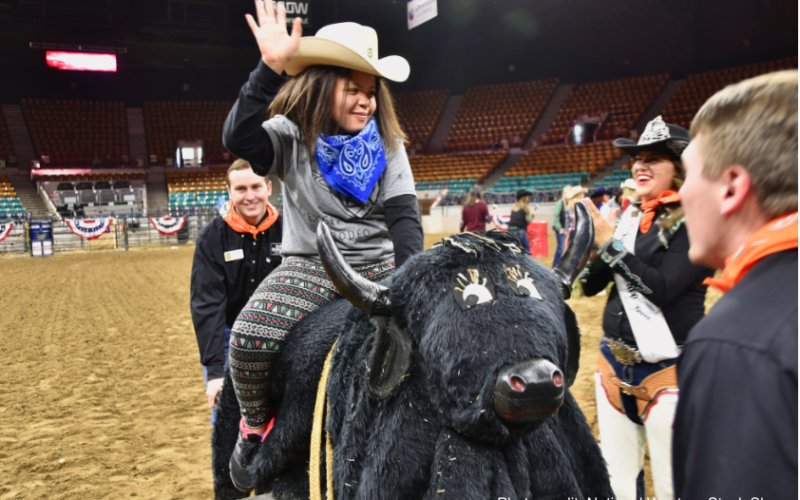 Exceptional Rodeo participant riding a fake bull.