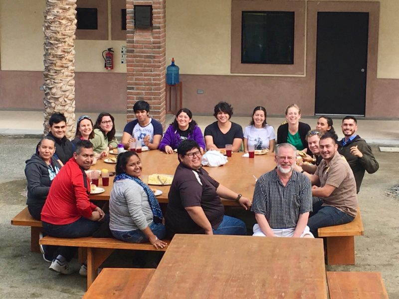 Group photo of fish pathology workshop participants around a table outside.