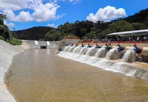 color photo of a new reservoir system in Brazil, with workers opening pipes and water rushing out