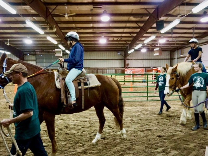 Volunteers lead student through adaptive riding exercise at Temple Grandin Equine Center Open House.