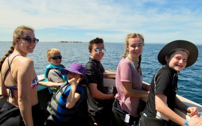 Five Todos Santos Center Family Adventure Week participants smiling from boat.