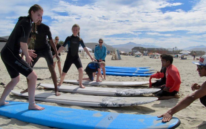 Todos Santos Center Family Adventure Week participants practice paddleboarding.