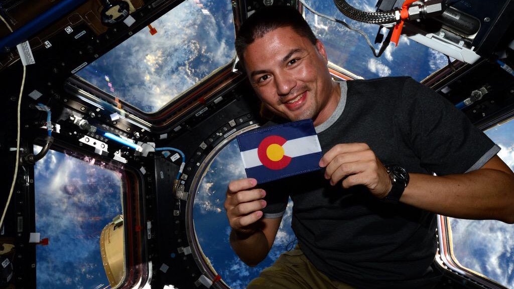Kjell Lindgren holding flag in space