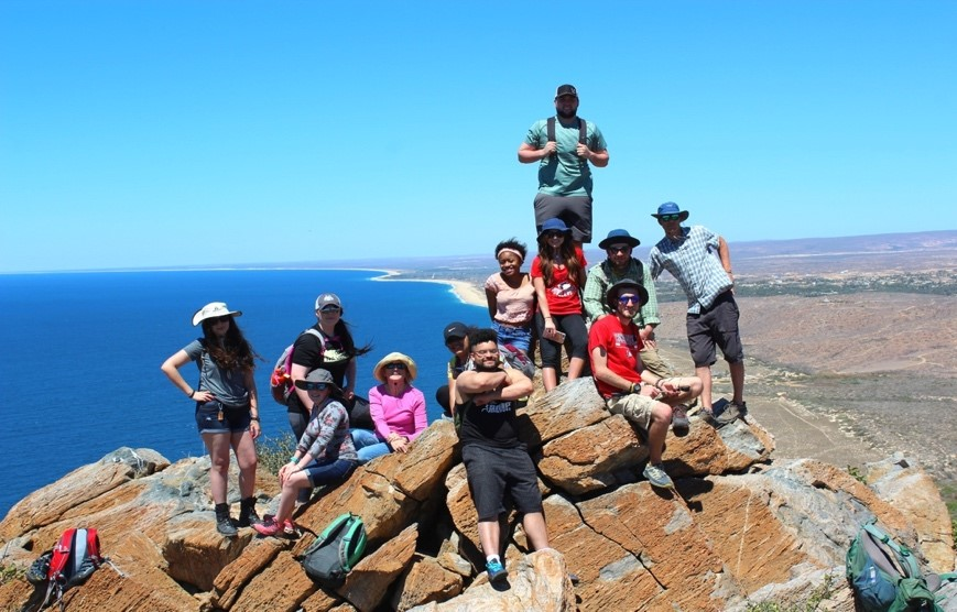 Group photo on a rock outcrop above the ocean.
