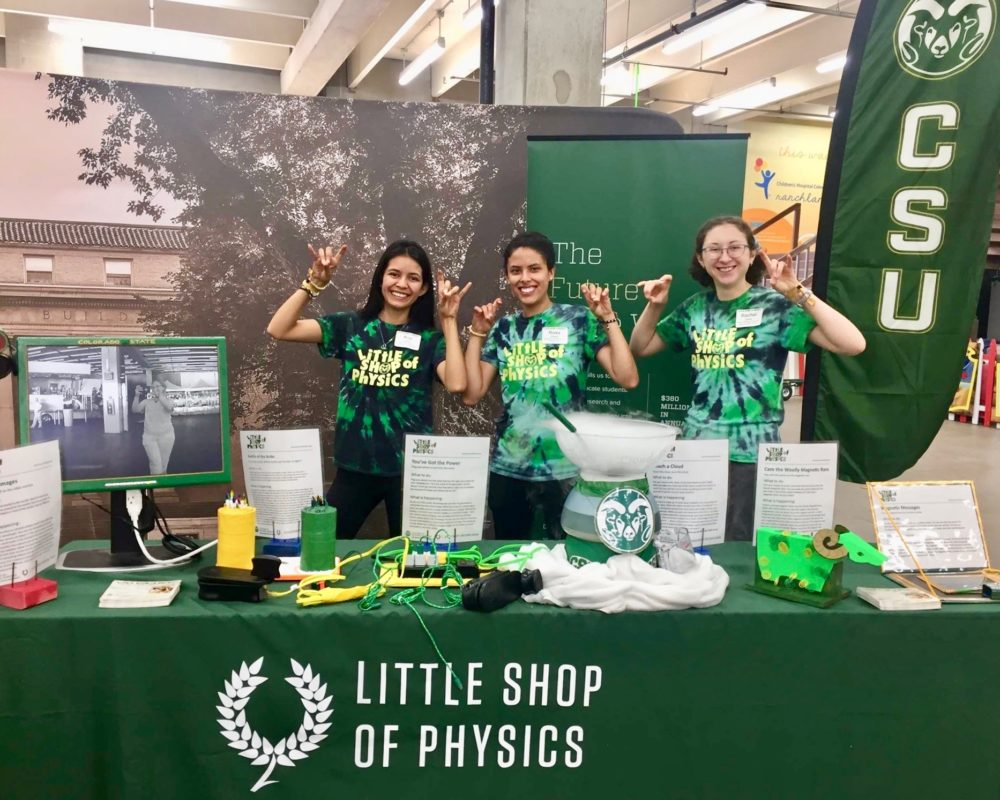Three team members from the CSU Little Shop of Physics smiling at CSU's booth at the 2018 Denver County Fair.