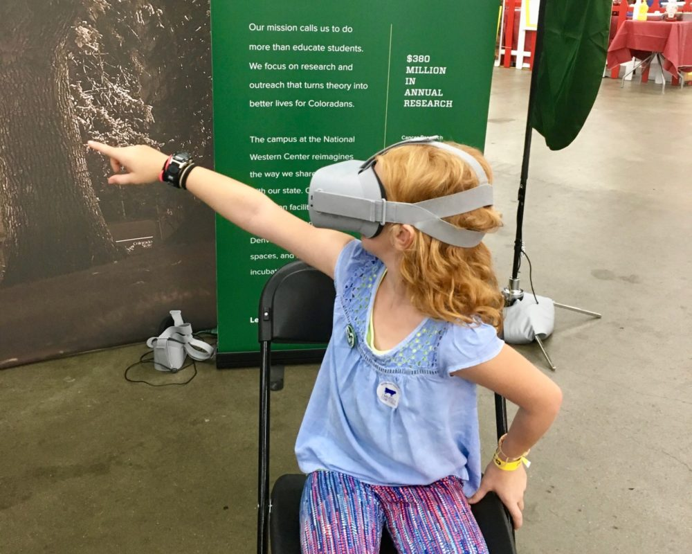 Young girl points into the distance wearing virtual reality headset at CSU's booth at the 2018 Denver County Fair.