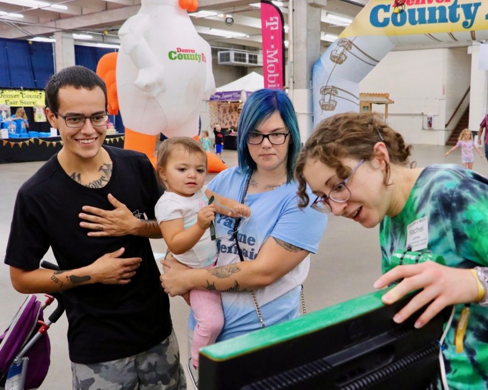 Denver County Fair attendees view infrared imaging screen with Little Shop of Physics team member at CSU's booth.