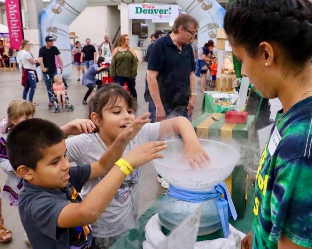 CSU Little Shop of Physics volunteer guides two young children through experiment at CSU's booth at the 2018 Denver County Fair.