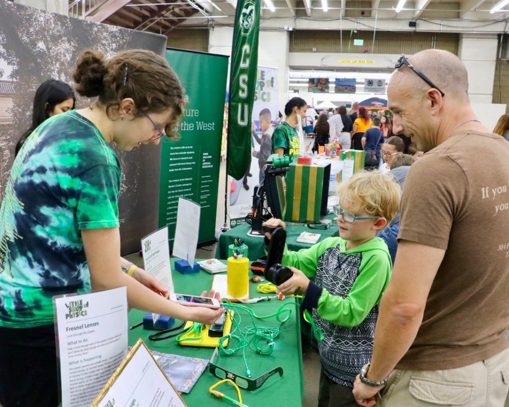 CSU Little Shop of Physics volunteers guide young boy and father through experiment at CSU's booth at the 2018 Denver County Fair.