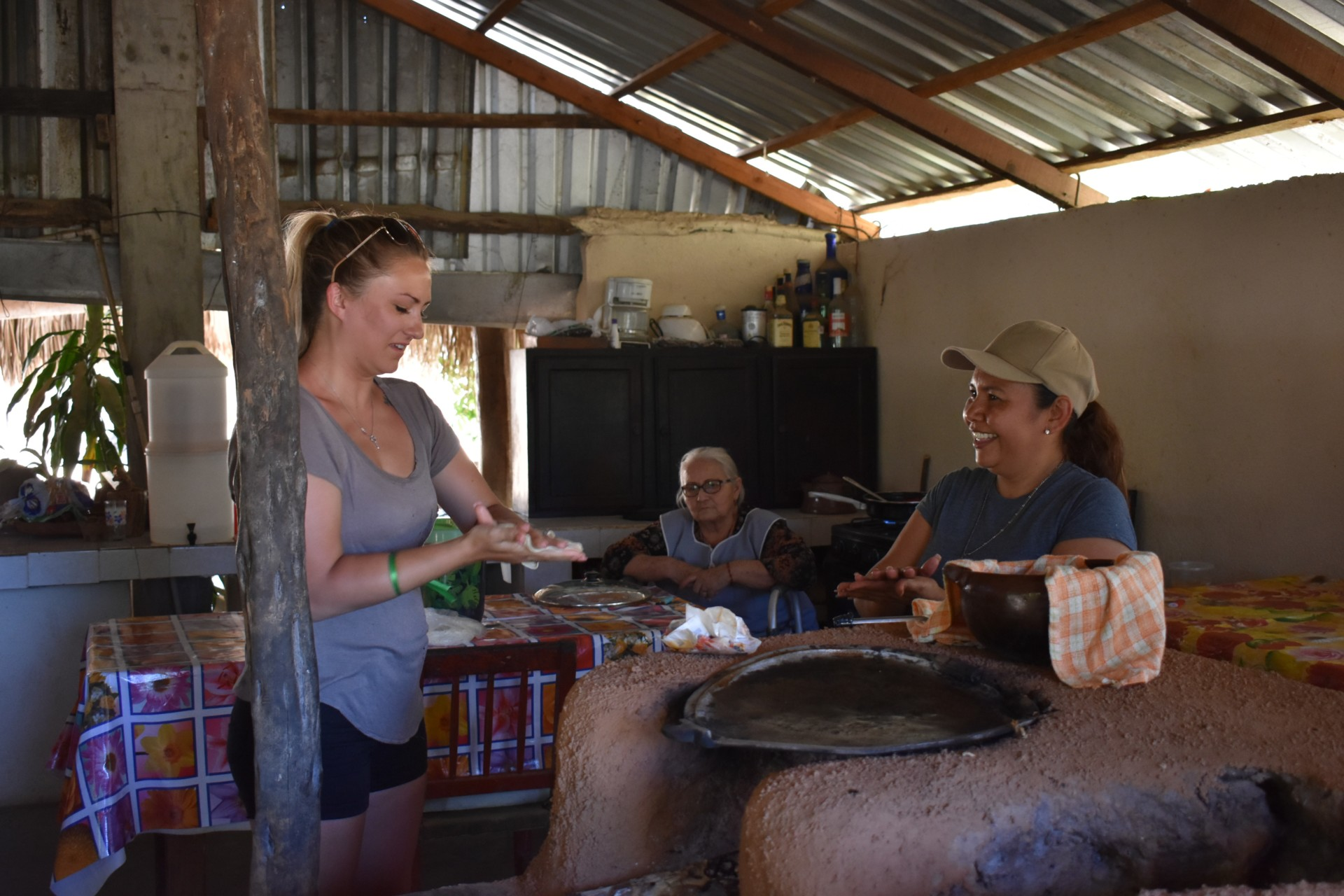 A student practices rolling a tortilla with a Todos Santos local.