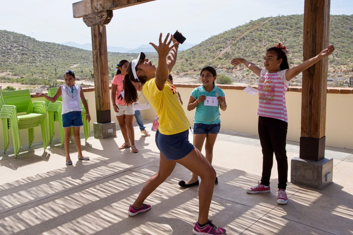 Kids Do It All instructor throws hands in air in middle of group of kids during activity outside CSU Todos Santos Center.