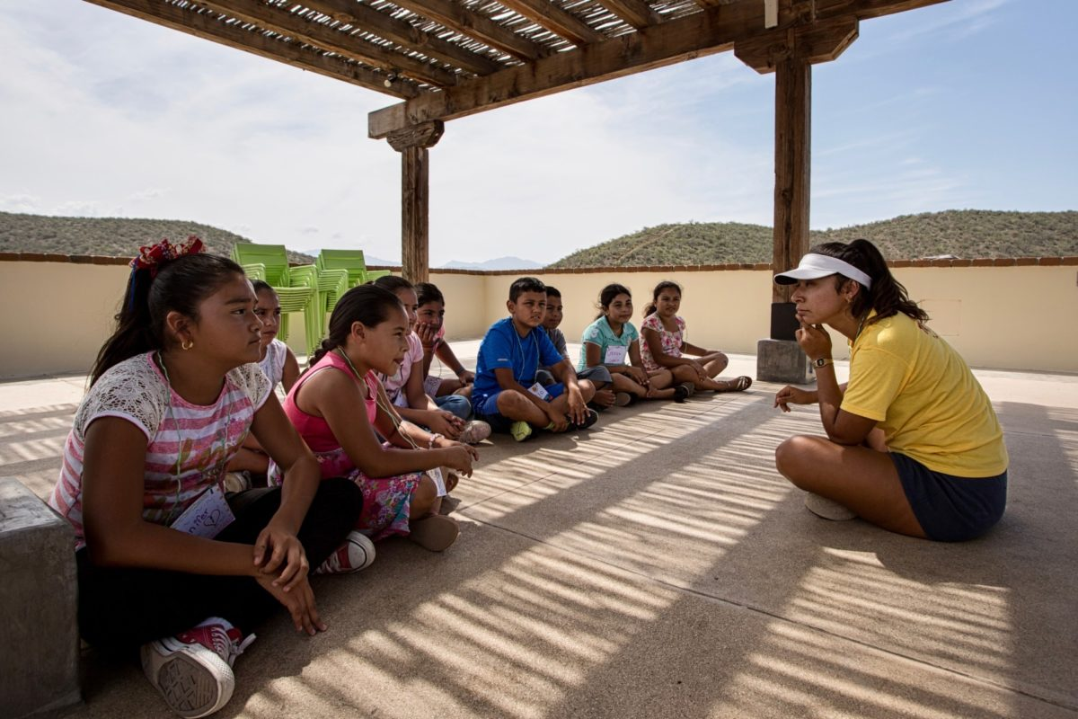 Kids Do It All instructor speaks with group of kids outside CSU Todos Santos Center.