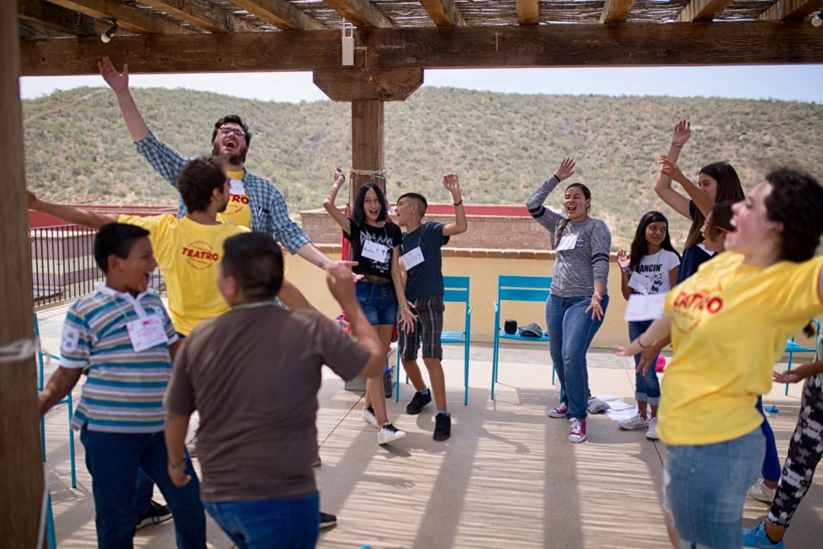 Kids Do It All instructor leads group of kids and other instructors during activity outside CSU Todos Santos Center.