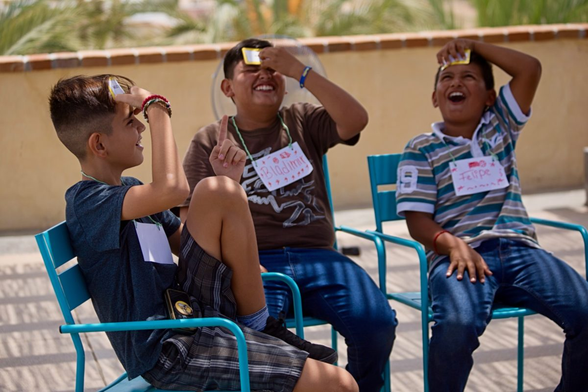 Three young boys laugh as they play game during Kids Do It All program at CSU Todos Santos Center.
