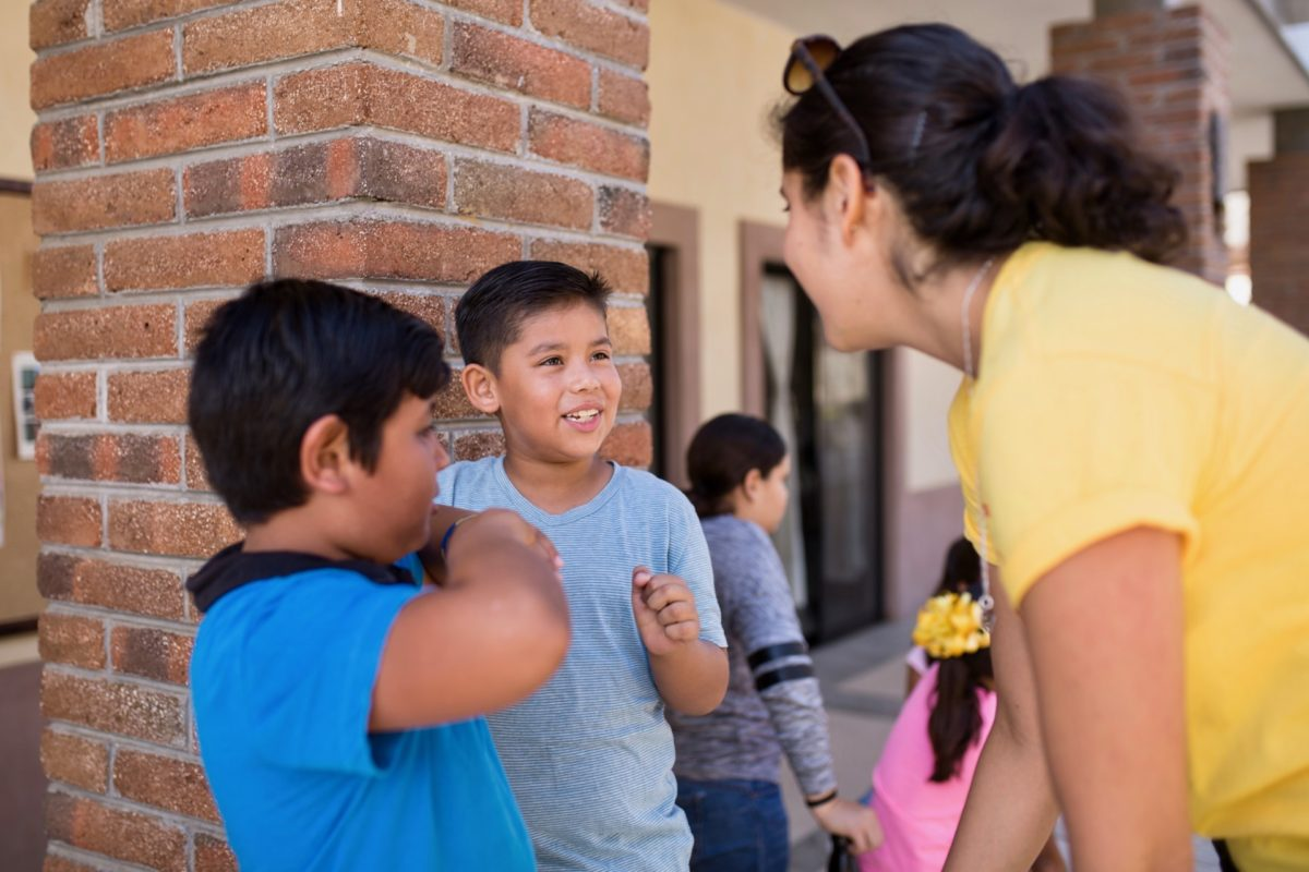 Kids Do It All instructor speaking with two young participants next to brick pillar at CSU Todos Santos Center.