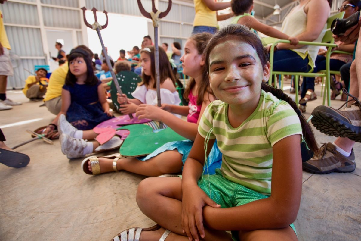 Young girl participating in the Kids Do It All program at the CSU Todos Santos Center smiles for camera during youth music-theatre performance.