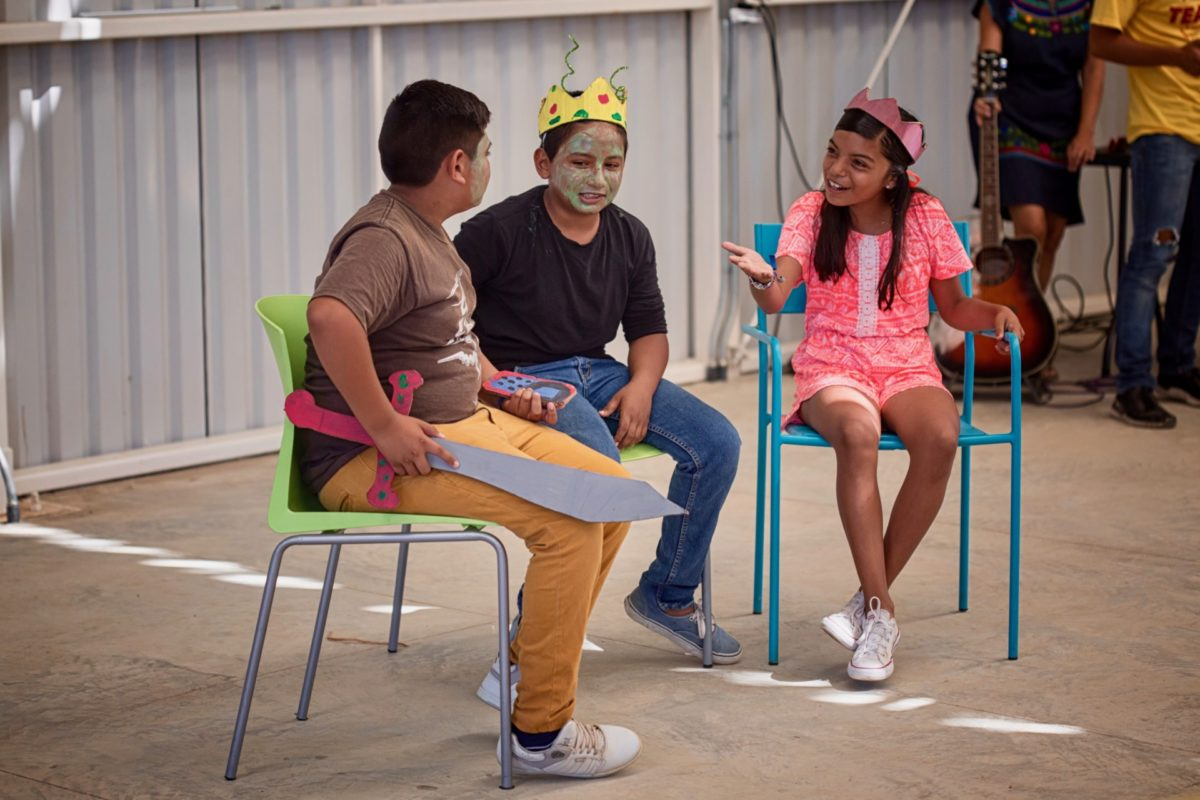 Three youth participating in the Kids Do It All program converse in front of crowd at the CSU Todos Santos Center during music-theatre performance.