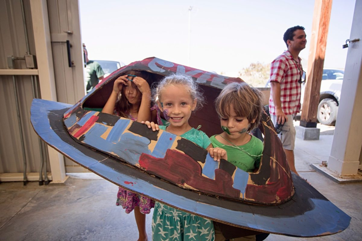 Three youth participating in the Kids Do It All program at the CSU Todos Santos Center smile inside papier-mâché UFO.