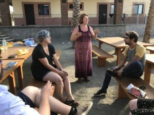 Heather Salyer in the Todos Santos Center courtyard, talking with two co-workers.
