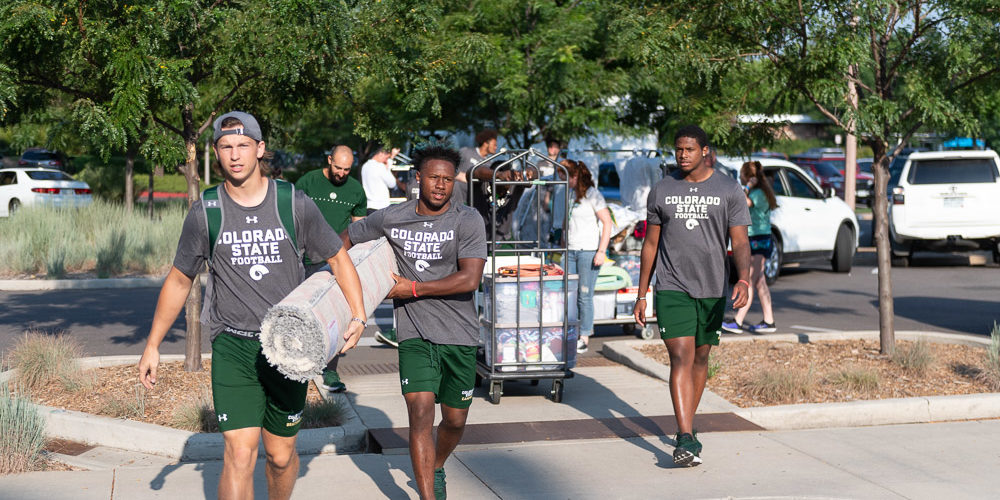 Football players help move stuff for students
