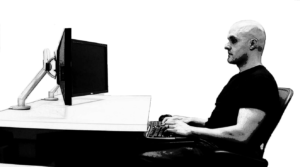 Person typing on keyboard looking at monitor screen