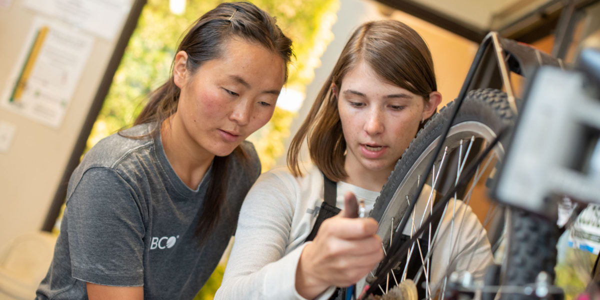 Bailey Richards, a mechanic at The Spoke, a student-run bike repair shop at Colorado State, assists a fellow student with a repair.