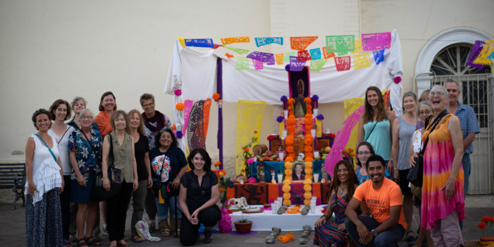 Participants of the 2018 Spanish & Culture Immersion Program at the CSU Todos Santos Center pose for group photo in front of Dia de Muertos altar.
