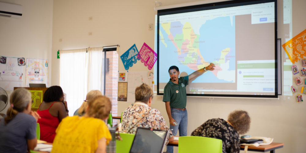 Olaf Morales, languages instructor, points out location on projected map during 2018 Spanish & Culture Immersion Program at the CSU Todos Santos Center.