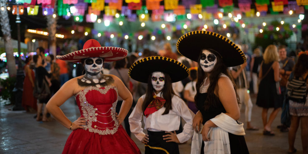Mexican girls dressed in traditional Dia de Muertos attire pose for photo during celebration near the CSU Todos Santos Center as part of closing ceremony for 2018 Spanish & Culture Immersion program.