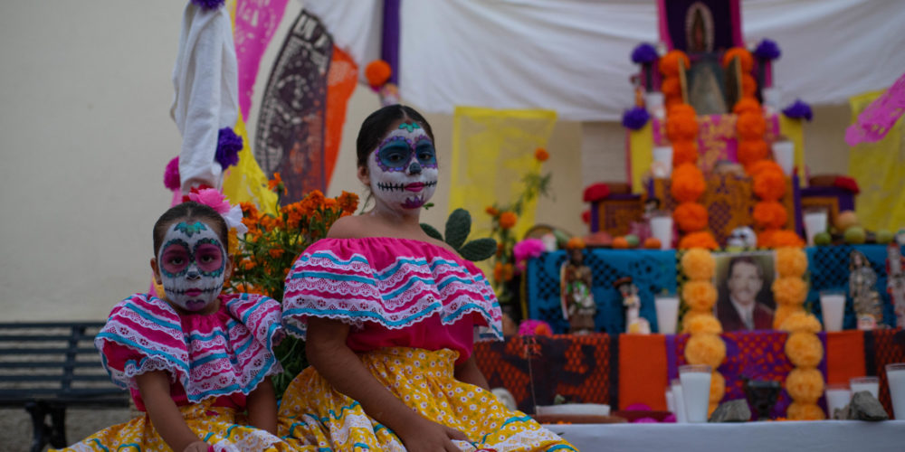 Mexican girls dressed in traditional Dia de Muertos attire pose in front of altar during at the CSU Todos Santos Center during 2018 Spanish & Culture Immersion program.