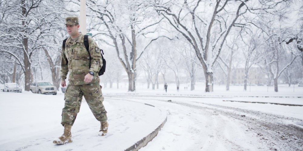 Student in fatigues on snowy Oval