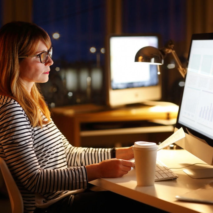 Portrait of businesswoman working late in front of a computer.
