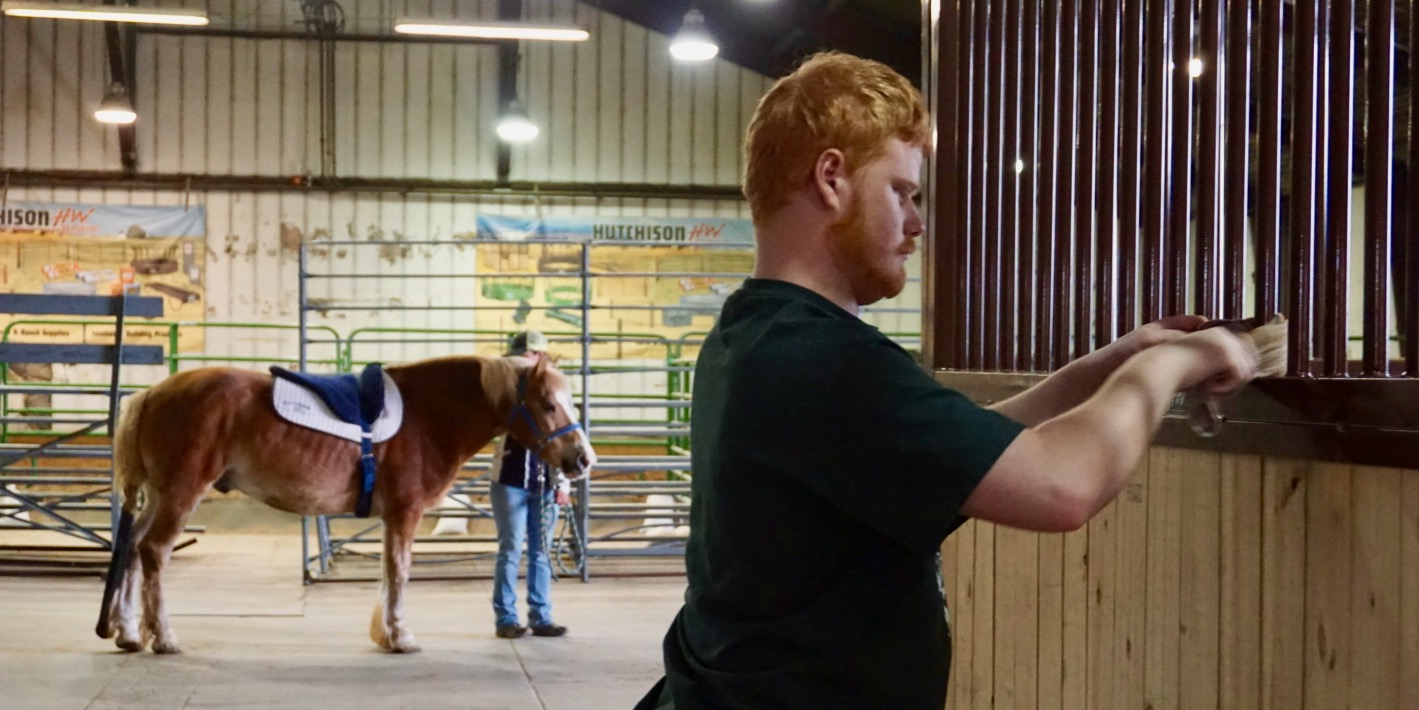 Michael McGrady dusts bars of horse stall at the CSU Temple Grandin Equine Center.