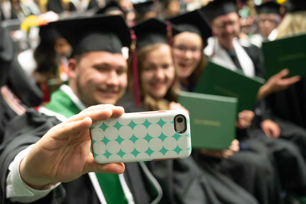 CHHS graduates take selfies with degrees during ceremony