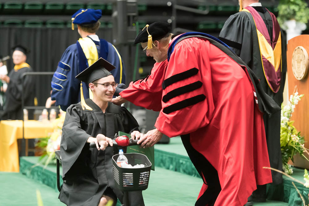 Dean John Hayes congratulates graduate in motorized chair