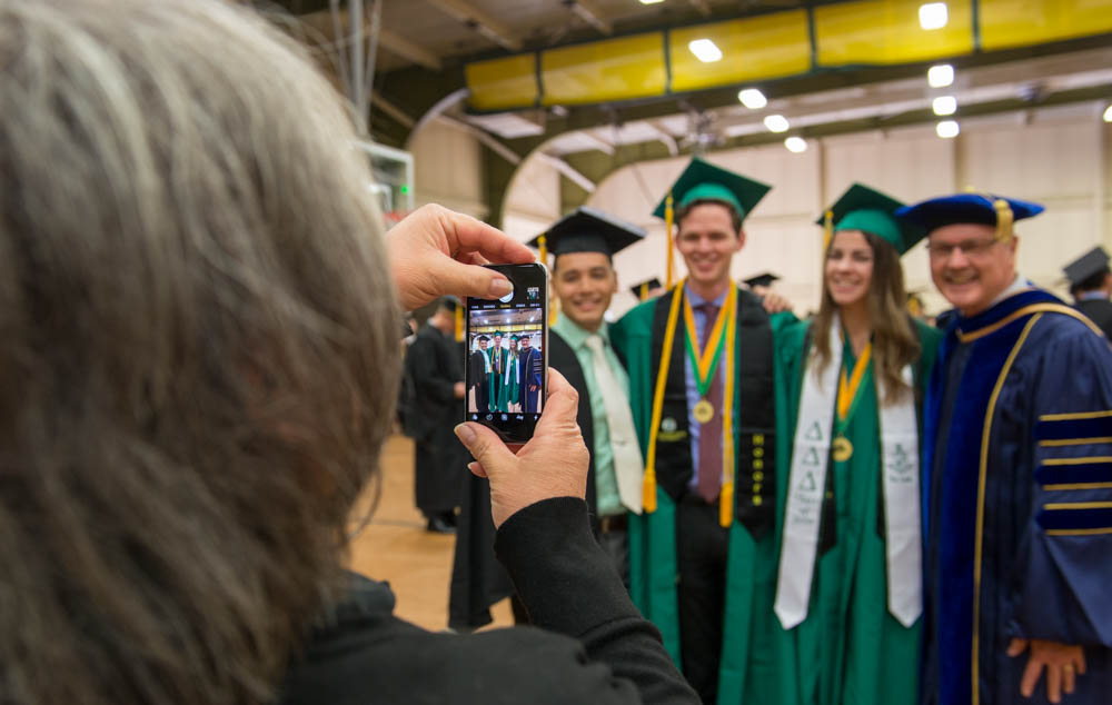 Graduates pose with professor for cellphone photo