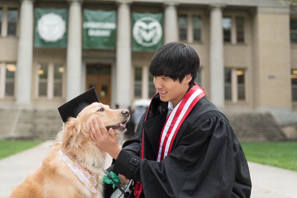 Graduate with dog wearing mortarboard in front of Admin building