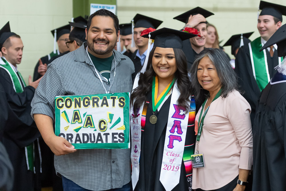 Graduate with family holding Congrats sign