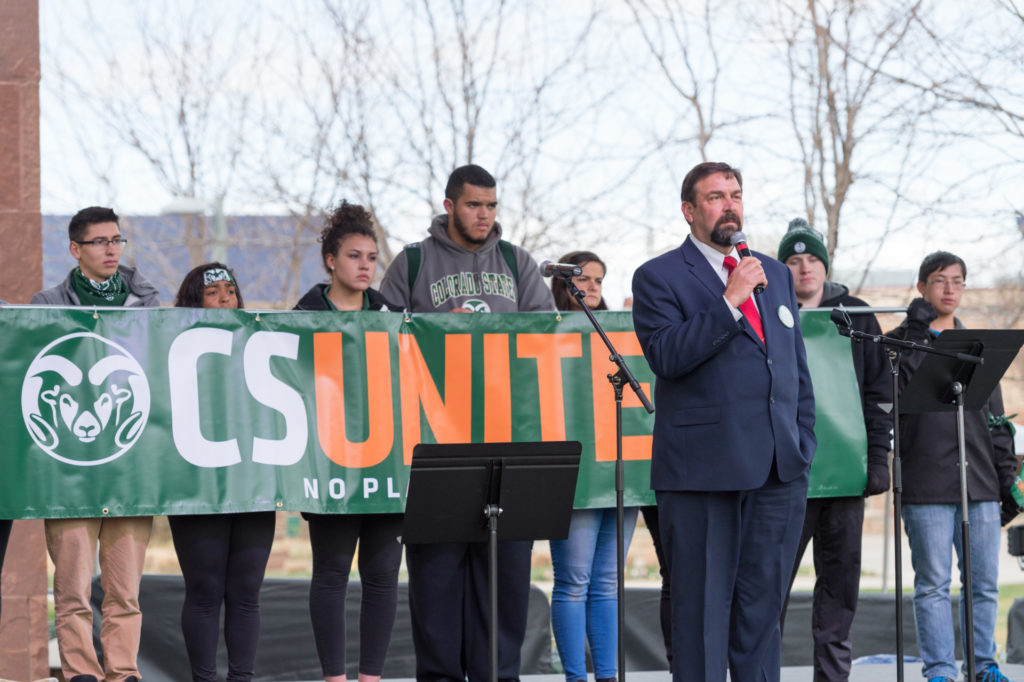 Tony Frank speaks in front of CSUnite banner held by students