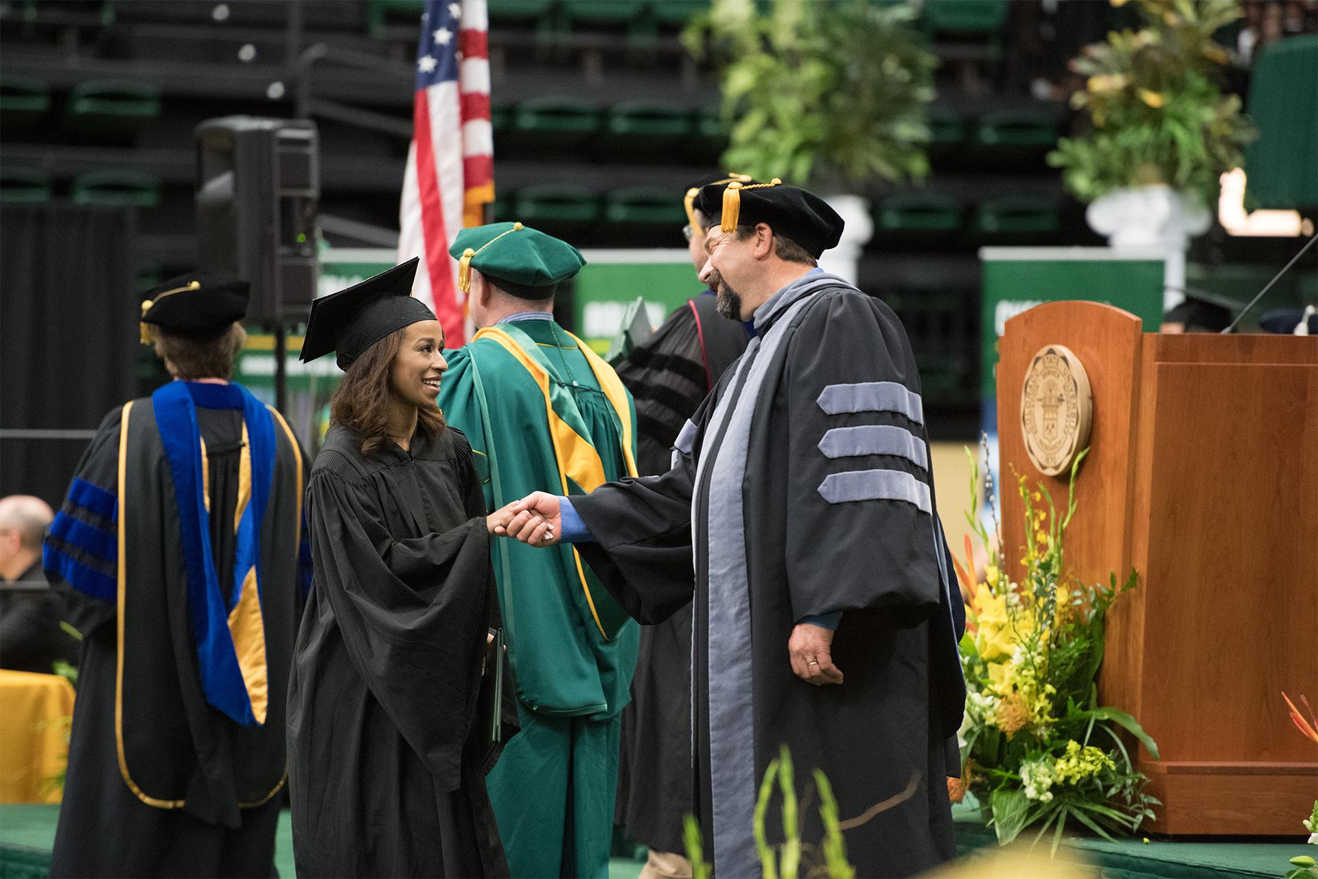 Tony Frank shakes hand of graduate