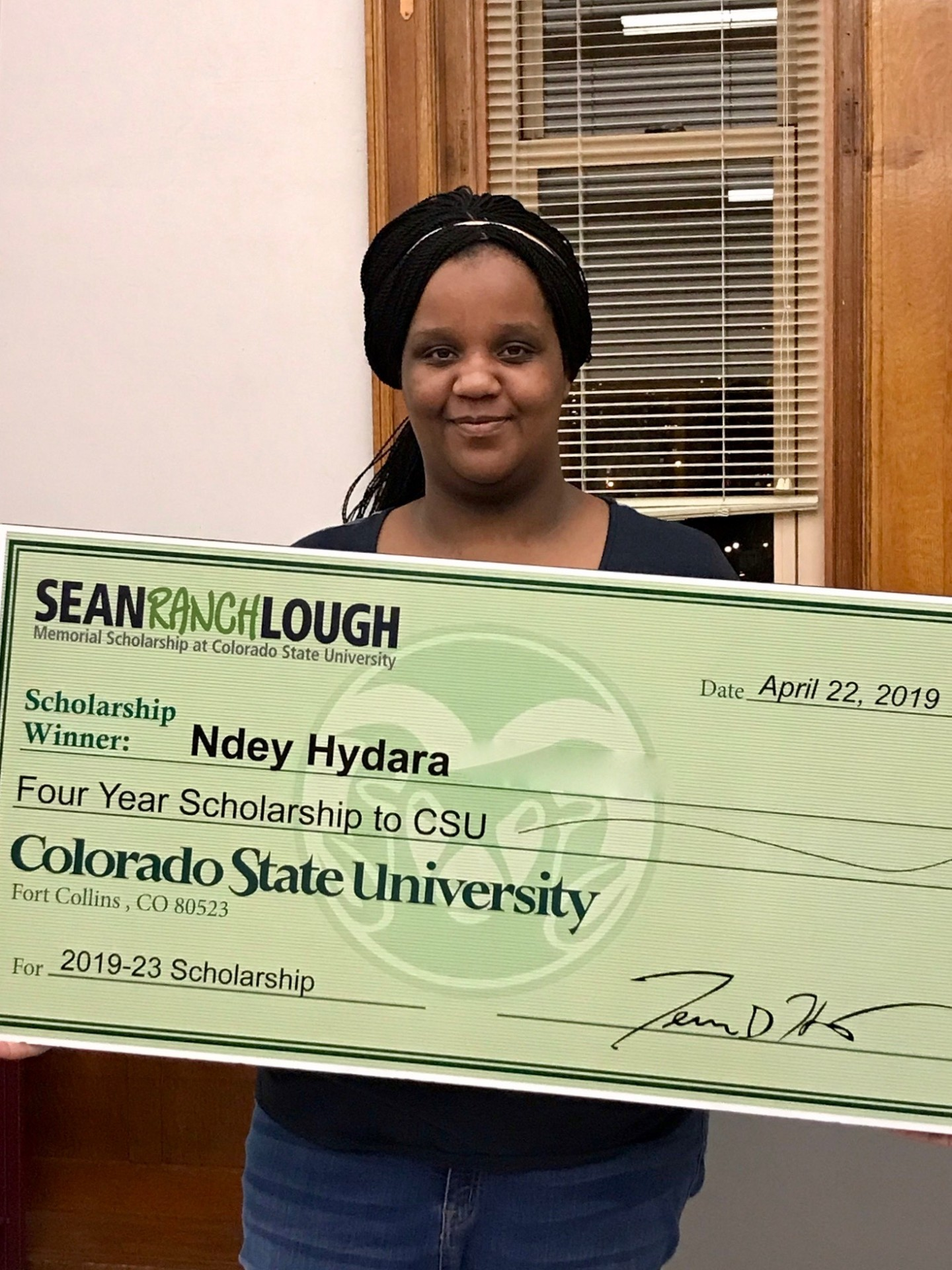 "Ndey Hydara holding Sean ""Ranch"" Lough scholarship check, which will cover the entire cost of her CSU tuition."