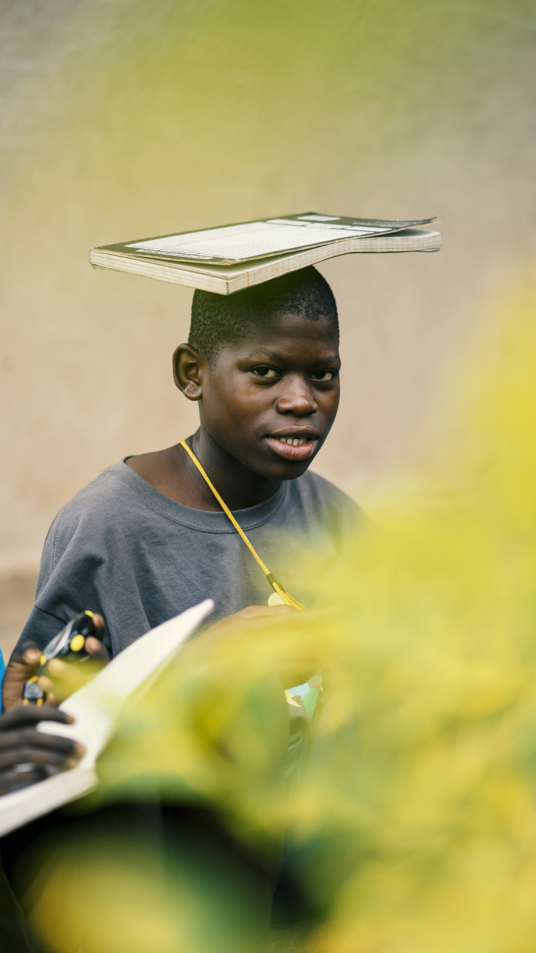 Student balancing notebook on head