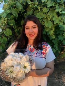 Andrea Sanchez holding white flowers.
