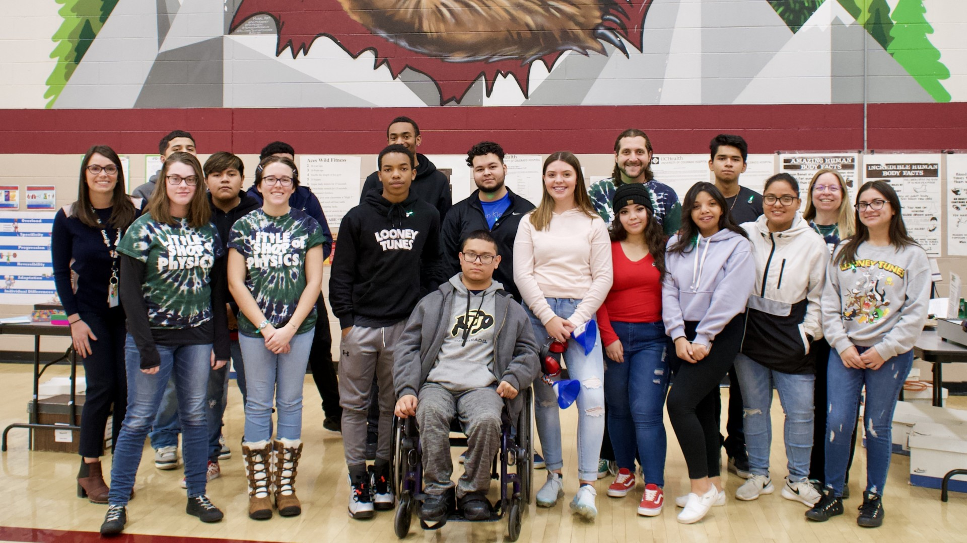 Little Shop of Physics 11th-grade mentors from Bruce Randolph School pose for group photo with LSOP team in gymnasium.