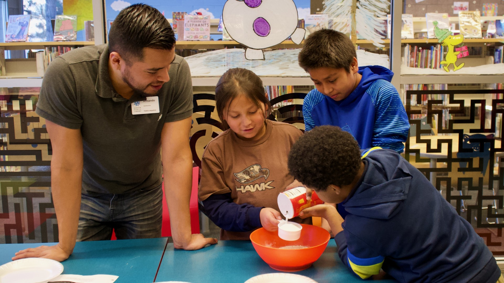 Library Program Associate Armando Pineche Rosales (far-left) engages youth participants during a STEM workshop on entomology led by CSU Denver Extension/4-H Agent Merielle Stamm (not pictured) at Valdez-Perry Branch Library in north Denver.